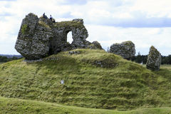 Castle Ruins With Men. An ancient ruined castle with three men sitting on top. This travel scene from Ireland is typical of many medieval buildings that have stock images
