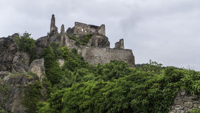 Castle ruins at top of rocky mountain stock image