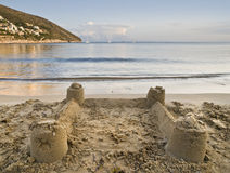 Castle on the Sand. Beach scene on a tranquil bay, with a castle of sand on the foreground and some sailboats on the horizon Royalty Free Stock Image