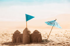 Castle in sand, flag and umbrella close-up on sea. stock photo
