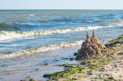 Castle of sand on the sea beach, horizon. Green algae stock images