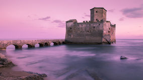 Castle on the sea. Abandoned Castle on a sea landscape at pink sunset Stock Photography