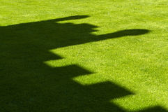 Castle shadow on grass. Black shadow of castle battlements on green grass Royalty Free Stock Images