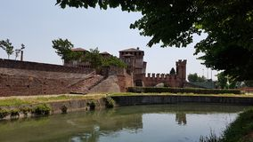 Soncino castle. Castle of Soncino seen from the back, reflecting itself on the deep green and blue water of the river Stock Image