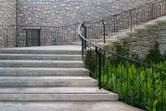 Castle style concrete curve stairways. With green fern and stone veneer wall Royalty Free Stock Photography