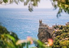 The castle of the swallow`s nest on a rock on the Black Sea in summer, Crimea. Symbol and landmark of the Crimea. A beautiful sce. Nic view through the foliage royalty free stock photos