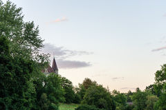 Castle tower can be seen through trees in sunset evening blue hour Royalty Free Stock Photo