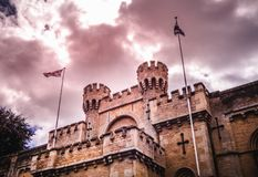 Castle Towers and Two Flagpoles With Flags Under Cloudy Sky royalty free stock images