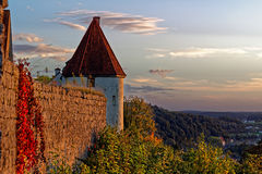 Medieval castle with view by autumn magic. Scenic late summer scenery at a medieval castle with view over the landscape by sunset. Waft of mist ascending from Stock Photos