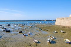 Castle view and beach full of small boats, low water stock photography