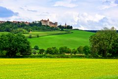 Castle and village behind rolling green hills, Burgundy, France. Castle and village of Chateauneuf en Auxois behind rolling green hills, Burgundy, France Royalty Free Stock Image