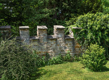 Castle wall with battlement in a garden. Part of a lower castle wall with battlements in a garden with bushes Royalty Free Stock Images