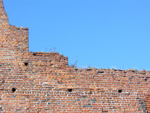Castle wall and blue sky. Old brick castle wall with visible damage against blue sky Stock Photo