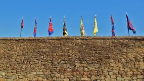 Castle Wall. Medieval castle flags sit still on a calm day outside of The Haemi Castle- Haemi, South Korea Stock Image