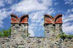Castle wall merlons. On a fortified wall in Italy with swallowtail shape and clouds on the background royalty free stock photos