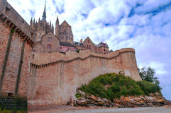 Castle wall of Mont Saint Michel. Castle wall of French village of Mont Saint Michel, in the near the sea on a cloudy day stock photos