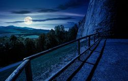 Castle wall and railing on a hill at night. In full moon light. view in to the beautiful mountainous landscape stock images