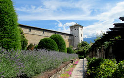 Castle wall and tower in Trento, Italy. Medival castle walls and tower in Trento, Italy. Fortificated wall and tower among the lavender flowers in the garden royalty free stock image