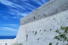 Castle wall in Tremiti islands with a group of people on the top whaching the seascape. For travel and tourism concept Royalty Free Stock Photos