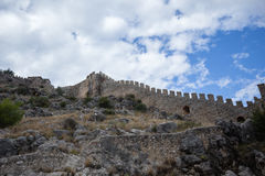 Castle walls of Alanya with tree branches. Castle walls of Alanya with blue sky and clouds Stock Image