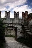 Castle walls with portal. Castle walls with battlements, merlons and wooden portals Royalty Free Stock Photo