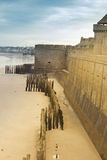 Castle walls of Saint Malo, France, over sea with pilings on the Stock Images