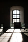 Castle window. Inside the Bratslava Castle, a window which lets the light enter and hit the ground, creating a great contrast between light and shadow stock image