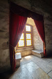 Castle window with curtains. Closeup of a castle window with stained glass and curtains Royalty Free Stock Photography