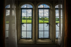 Castle Window Frame and landscape. The view from a castle window showing the lake and sunny landscape beyond. Window is dressed with period curtains and netting royalty free stock photos