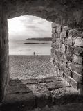 Castle window. Lone figure at waters edge seen through a castle window, black and white stock photography