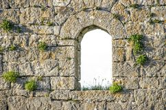 Castle window in Skodra castle. Castle window surrounded with carved stones and grass in cracks in Skodra castle royalty free stock image