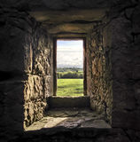 Castle Window. View through a stone castle window to green fields in Ireland stock photo