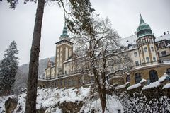 Castle in winter forest in Lillafured, Miskolc, Hungary. Snowy forest and rocks around historical luxury palace. Travel and winter vacation in Europe royalty free stock image