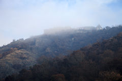 Castle on a wooded hill in the fog. Landscape Stock Image