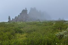 Castles of mountain spirits are cliffs in the fog located in vicinity of Karakol lakes. Altai Krai. Castles of mountain spirits are cliffs in the fog located in Stock Photos