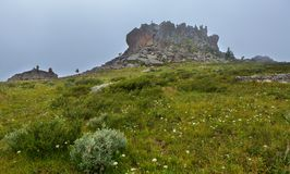 Castles of mountain spirits are cliffs in the fog located in vicinity of Karakol lakes. Altai Krai. Castles of mountain spirits are cliffs in the fog located in Royalty Free Stock Images