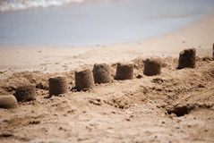 Castles on the sand. A series of small castles on a sandy beach Royalty Free Stock Photos