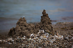 Castles in the Sand. Sandcastles and shells scattered on the beach Stock Photos