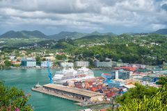 Castries, st.lucia - November 26, 2015: Ocean liner in sea port on mountain landscape. Town on blue sea shore with cloudy sky. Lux. Ury travel on ship, water Royalty Free Stock Image