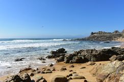Wild beach with rocks, big waves and prehistoric settlement ruins. Sunny day, Barona, Galicia, Spain. Castro de Barona, Galicia, Spain. Wild beach with rocks royalty free stock photography