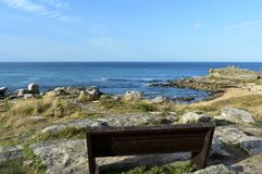 Castro de Barona, Galicia, Spain. Wooden bench on a cliff and prehistoric settlement ruins with beach and rocks. Sunny day. Wooden bench on a cliff. Beach and royalty free stock image