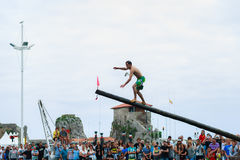 CASTRO-URDIALES, ESPAÑA - 29 DE JUNIO: El muchacho no identificado llega la bandera en la competencia del polo grasiento celebrad Foto de archivo libre de regalías