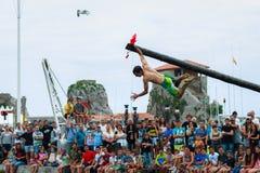 CASTRO URDIALES, SPANIEN - 29. JUNI: Der nicht identifizierte Junge, der die Flagge im Wettbewerb des schmierigen Pfostens hält,  Stockbild