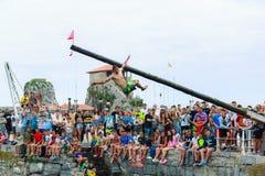 CASTRO URDIALES, SPANIEN - 29. JUNI: Nicht identifizierter Junge fällt vom schmierigen Pfosten zum Meer im Festival, das herein a Lizenzfreie Stockbilder