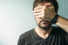 Casual adult male covering face and eyes with hand. Portrait of casual adult male covering face and eyes with hand, selective focus Royalty Free Stock Image