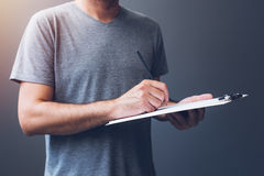 Casual adult male writing notes on notepad paper Royalty Free Stock Image