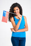 Casual afro american woman holding USA flag. Portrait of a happy casual afro american woman holding USA flag isolated on a white background and looking at camera Royalty Free Stock Photos