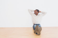 Casual Afro man sitting on floor as he looks up to the wall Royalty Free Stock Photography