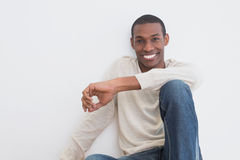 Casual Afro young man sitting against a wall Royalty Free Stock Images