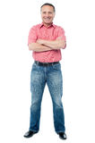 Casual aged man standing on white background. Full length image of mature man standing with folded arms Royalty Free Stock Images